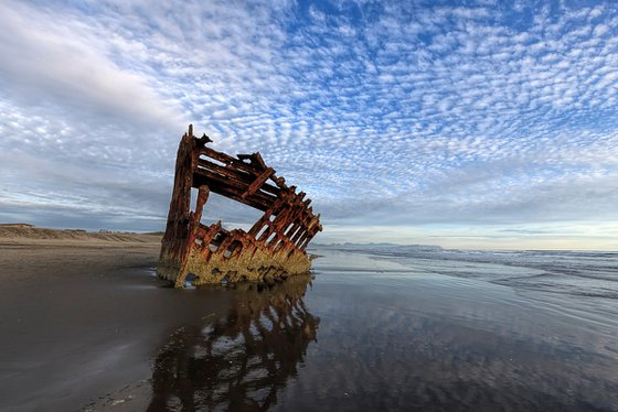 Peter Iredale shipwreck under a partly cloudy blue sky.