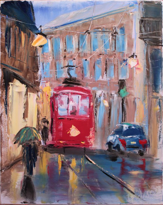 Rainy day in old city with red streetcar