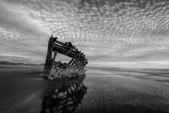 Peter Iredale shipwreck under a partly cloudy sky.