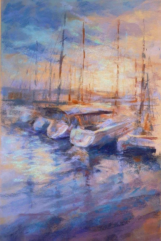 Sailing boats in marina at sunset