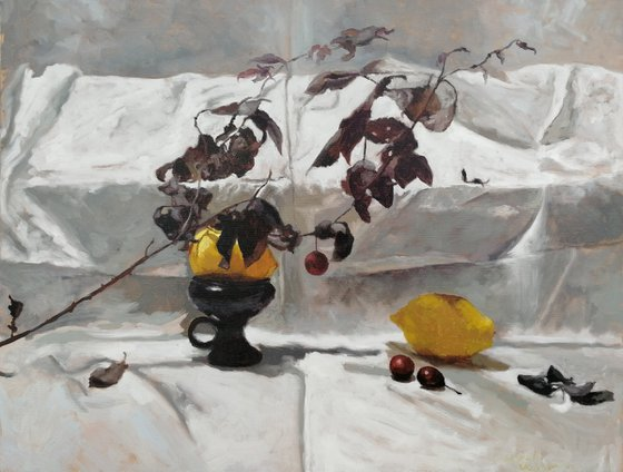 A composition with two lemons and a plum twig
