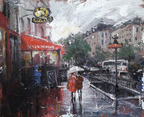 A couple under an umbrella. Сityscape. Rainy city