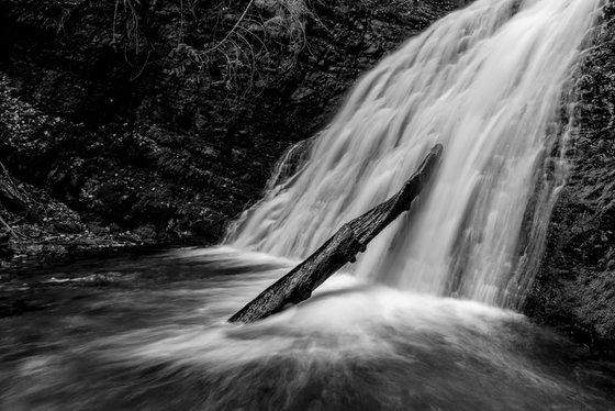Log lays against waterfalls.